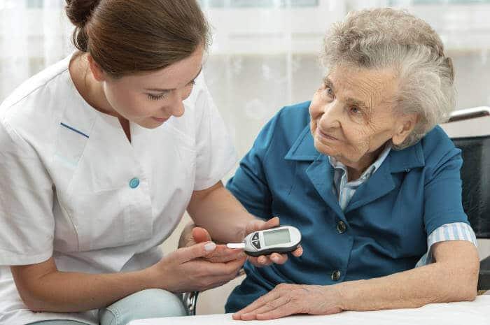 Caregiver Testing Senior Womans Blood Sugar